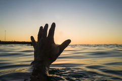 Hand coming out of water Stock Photo
