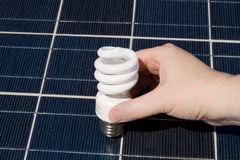 Hand Compact Fluorescent Light Bulbs Solar Panel Royalty Free Stock Image