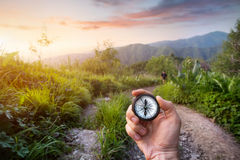 Hand with Compass in the mountains. Hand with compass at mountain road at sunset sky in Kazakhstan, central Asia Royalty Free Stock Photography