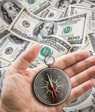 Hand with compass over hundred dollars. Finance concept. Stock Photos