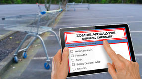Hand completing Zombie Apocalypse survival checklist on a computer tablet - infront of empty supermarket carpark. Hand completing Zombie Apocalypse survival Royalty Free Stock Images