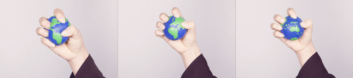 Hand compressing planet Earth. Variants of all continents. Stock Photos