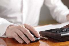 Hand on computer mouse next to the keyboard Stock Photo