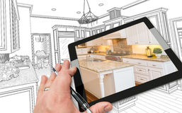 Hand on Computer Tablet Showing Photo of Kitchen Drawing Behind. Stock Image
