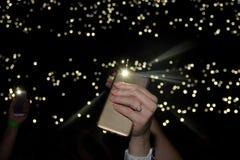 Hand concert shine a flashlight Stock Photos