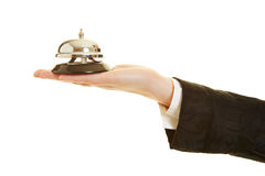 Hand of concierge holding hotel bell Royalty Free Stock Photo