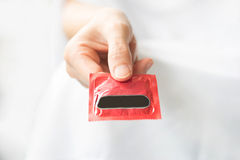 Hand with condom Royalty Free Stock Photography