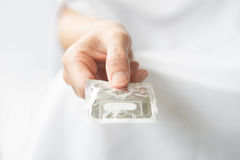 Hand with condom Royalty Free Stock Image
