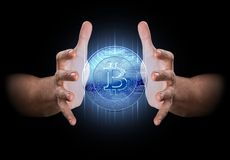 Hand Conjuring Cryptocurrency. A pair of male hands enveloping a hologram of a bitcoin on an isolated dark background Royalty Free Stock Photos