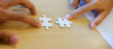 Hand connecting couple puzzle piece. Teamwork, Partnership, successful royalty free stock photo