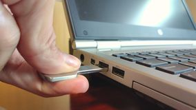 Hand connecting USB flash drive to laptop computer