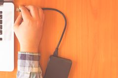 External hdd. Hand connects a external hdd cable to laptop for recovery data royalty free stock images