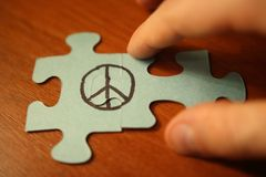 Hand connects puzzles of sign of peace. World Day of Peace. Royalty Free Stock Photos