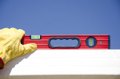 Hands with gloves on spirit level outdoor construction Royalty Free Stock Photos