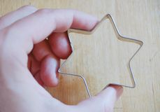 Hand and cookie cutter Stock Photos