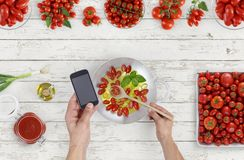 Hand cooking fry and mix tomatoes sauce above saucepan with phone on kitchen wooden white work top, copy space, top view stock images