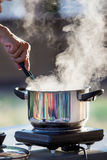 Hand cooking on hot pot with water steam Royalty Free Stock Photo