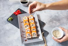 Hand cooking sushi set on concrete table. Top view stock image