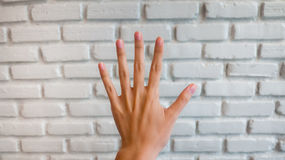 Hand count number five. With white brick background, soft focus Stock Photo