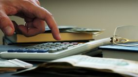 Hand counting on a calculator and money on a desk. stock video footage
