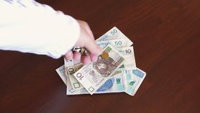 Polish zloty - zl money banknotes and coins. Hand counting official currency of Poland in denominations of 10, 20 & 50 zloty bills with groszy bronze and nickel stock footage