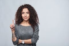 Hand counting - one finger. Curly woman pointing up at blank copy space royalty free stock photos