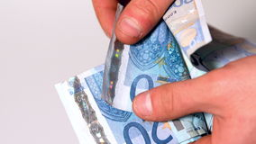 Hand counting wad of twenty euro notes Stock Photo