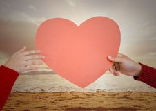 Hand of couple holding red heart on beach royalty free stock photo