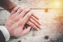 Hand in hand. Couple in love showing affection on summer day. Hand in hand. Couple in love showing affection on summer day at sunset. Wearing wedding rings Royalty Free Stock Images