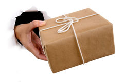 Hand of courier or mail man delivering or giving parcel through torn white paper background Royalty Free Stock Photo