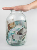 Hand covered three-liter jar with Russian money Royalty Free Stock Photography