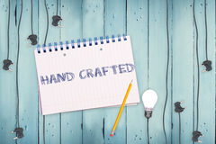Hand crafted against notepad and plug on wooden background Royalty Free Stock Photography