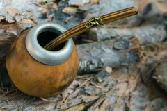 Hand Crafted Artisanal Yerba Mate Tea Leather Calabash Gourd with Straw on Wood Logs in Forest. Travel Wanderlust Concept. Earthy. Tones. Traditional royalty free stock photo