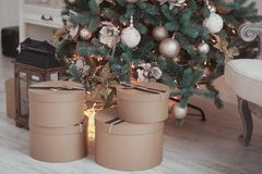 Hand crafted brown paper gifts on rustic wooden floor under Christmas tree. stock photos