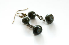 Hand crafted earrings. Made with metal and black stones isolated on the white background Stock Image