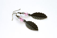 Hand crafted earrings. Made with metal leaves and pink crystals isolated on the white background Stock Photos