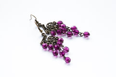 Hand crafted ethnic earrings. Made with metal and violet crystals  on the white background Royalty Free Stock Image