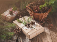 Hand crafted gift on rustic wooden background and a basket with fir branches and cones Stock Image
