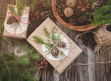 Hand crafted gift on rustic wooden background and a basket with fir branches and cones, top view Stock Images