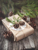 Hand crafted gift on rustic wooden background with with fir branches and cones Royalty Free Stock Photos