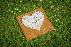 Hand crafted heart on wooden plank. Nice home made wool heart on wooden plank lying on grass Royalty Free Stock Photography