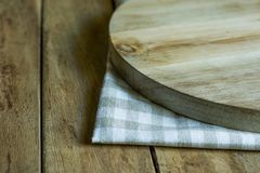 Hand Crafted Round Wood Cutting Board on Folded Cotton Checkered Kitchen Towel Plank Table Stock Images