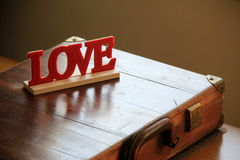 Hand crafted wood endearment that reads 'Love' set on man's briefcase Royalty Free Stock Images