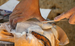 Hand of a craftsman and stone sculpting. Hand of an expert craftsman and stone sculpting royalty free stock photos