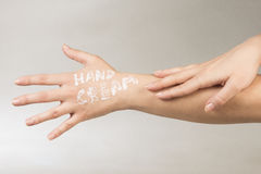 Hand cream on hand. Letters of hand cream from white hand cream are on female hand on gray background Stock Photography