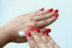 Hand cream on hand with red manicure on pastel blue background. Female hand care. stock images