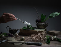 Hand cream with a spoon, dish of spinach on the table, old silver vase. black background Stock Photos