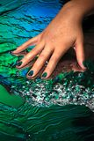Hand with creative nail design laying on water background. A hand with creative nail design on a green and blue water background with waves and light sparkles stock images