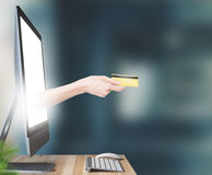 Hand with credit card comes out of computer. Hand with credit card, shopping on line stock image