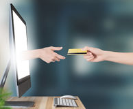 Hand with credit card comes out of monitor. Hand with credit card, shopping on line stock photography